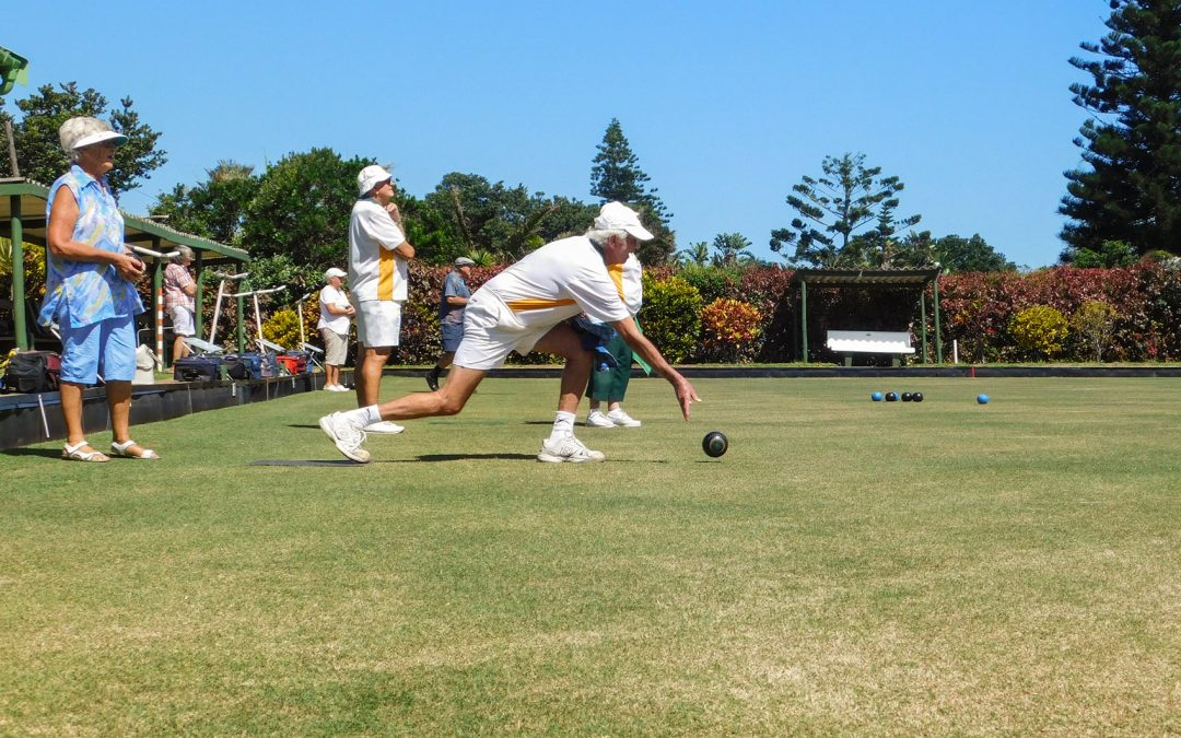 A bowler rolls a lawn ball towards the jack