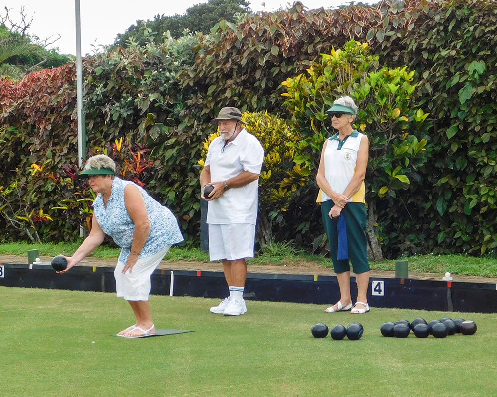 Lawn bowls player preparing to roll her ball